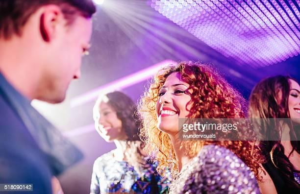 Teen girl flirting with a guy in a night club
