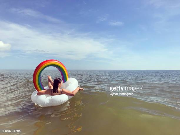 teen girl floating in a rainbow inner tube in the ocean - offbeat stock pictures, royalty-free photos & images