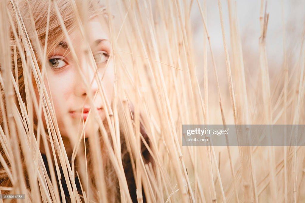 Teen girl hidden in tall grass, eyes looking at you : Stock Photo