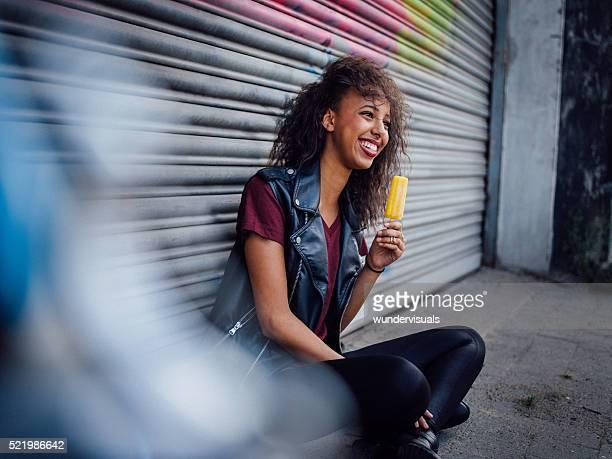 Teen girl holding an orange flavoured ice on city street