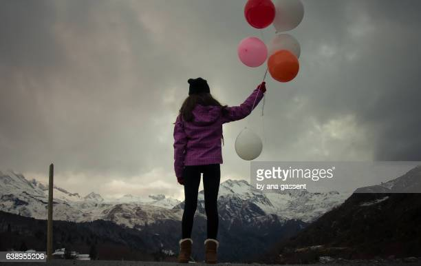 Teen girl holding colour balloons
