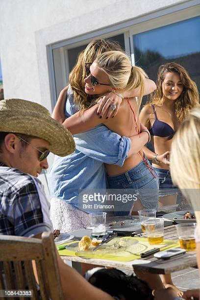 Teen girl hugs teen girl at BBQ table