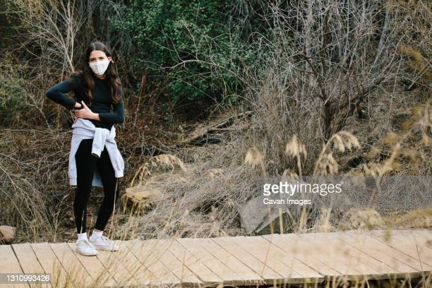 teen girl in a mask appears irritated while outside on a wooden bridge - thousand oaks stock pictures, royalty-free photos & images