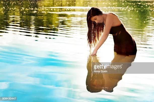 Teen girl in brown dress stands in lake at sunset