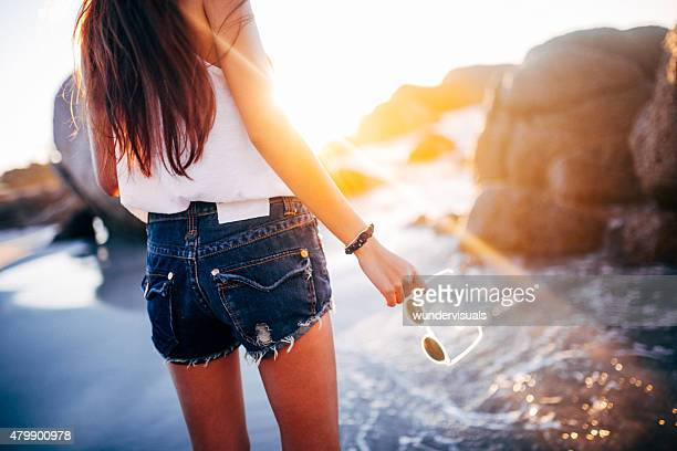 Teen girl in denim shorts at the beach with sunglasses
