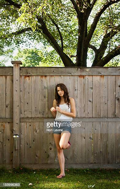 Teen girl in front of wooden fence, portrait