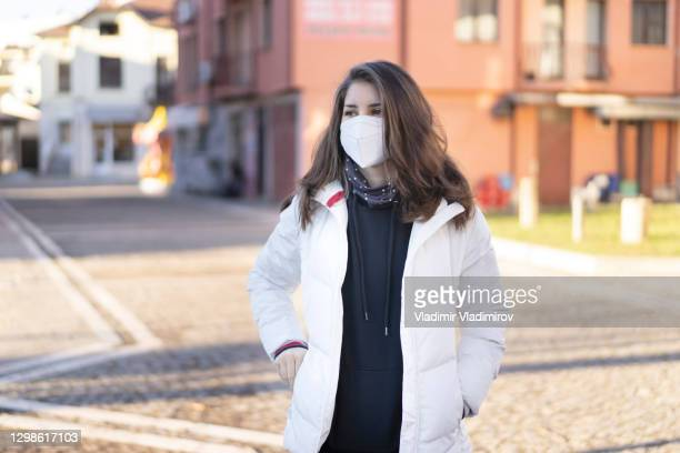 teen girl in white jacket and mask portrait - department of health and human services stock pictures, royalty-free photos & images