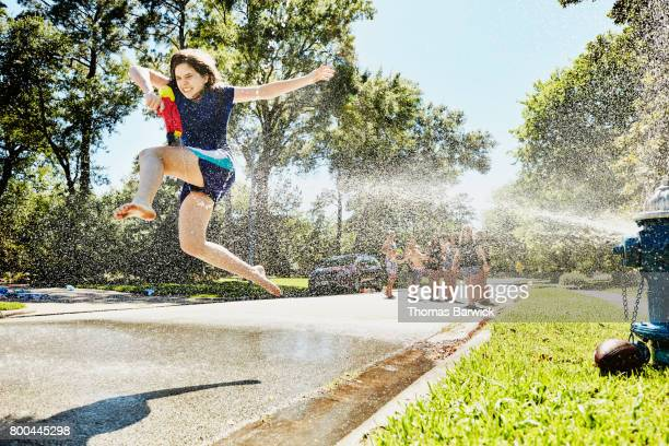 Teen girl jumping through spray from fire hydrant on summer afternoon