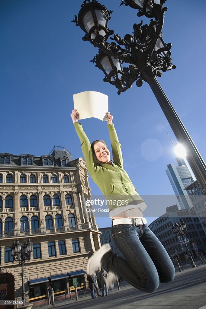Teen girl jumping with sign : Foto de stock