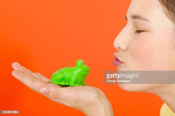 Teen girl kissing a toy frog