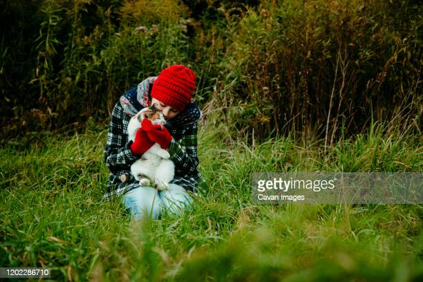 teen girl kissing her cat on a cold fall day in michigan - cat with red hat stock pictures, royalty-free photos & images