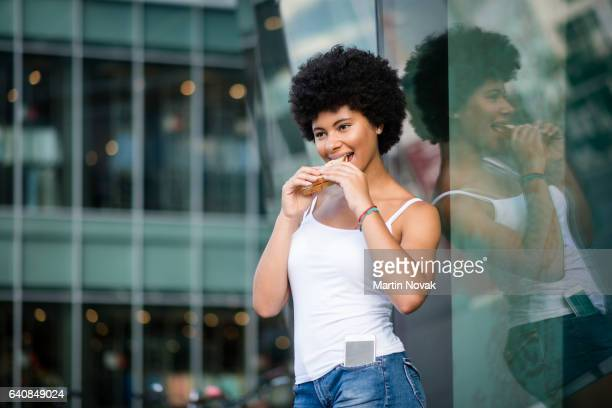 Teen girl leaning against large glass window. Eating sandwich.
