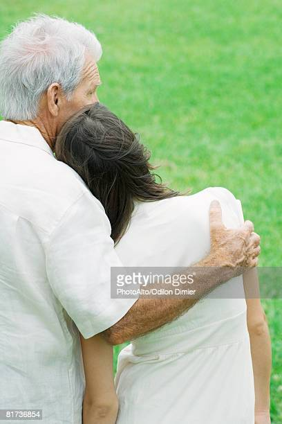 Teen girl leaning head on grandfather's shoulder, rear view