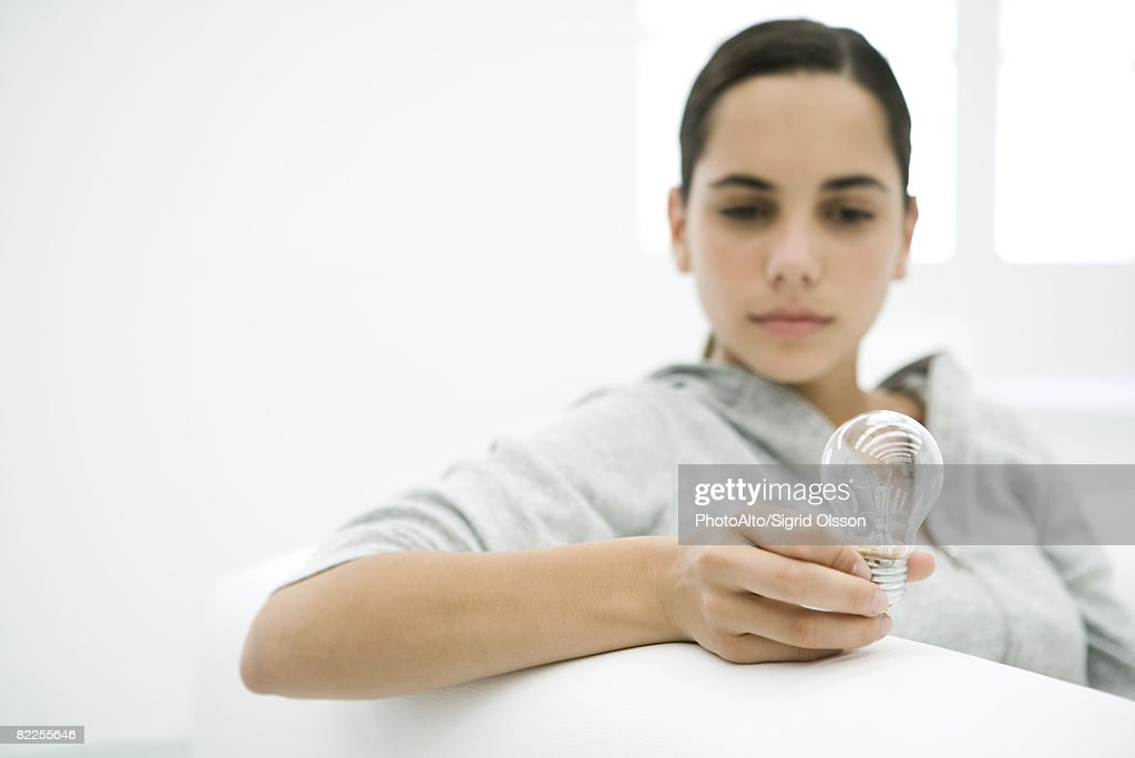 Teen girl looking at light bulb, focus on foreground : Stock Photo