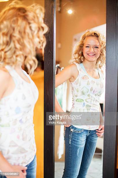 Teen girl looking in mirror in clothing boutique.