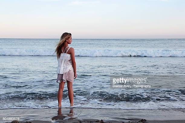 Teen girl looking out at ocean