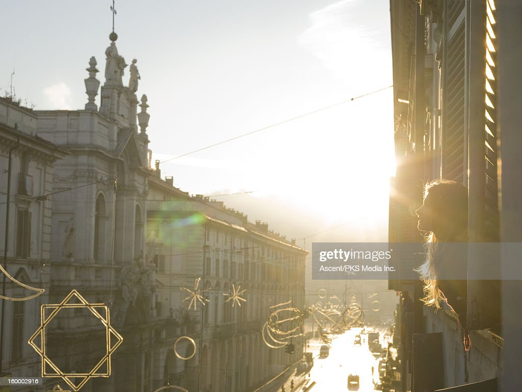Teen girl looks out window above street, sunrise : Stock Photo