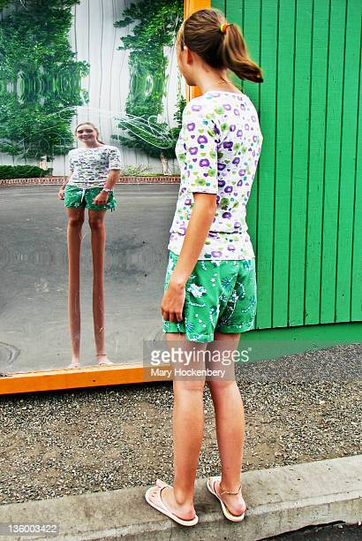 teen girl loooking at distorting mirror - fun house stock pictures, royalty-free photos & images