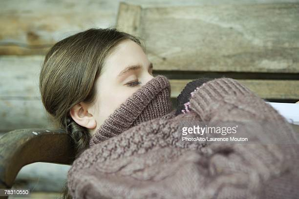 Teen girl lying down with turtleneck pulled up over face and mouth, eyes closed