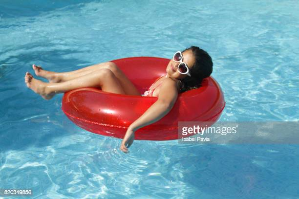 teen girl lying in inner tube in pool - red tube stock photos and pictures