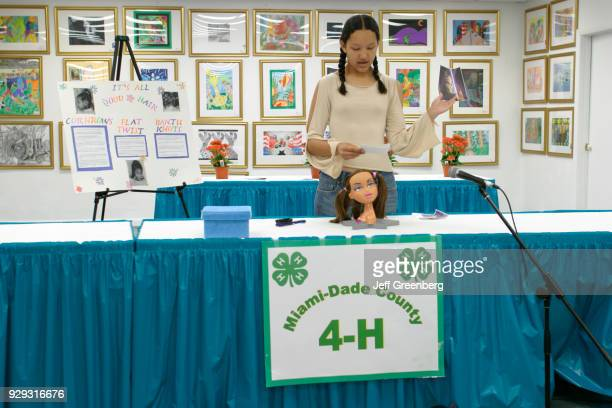 A teen girl makes a hairstyling presentation at the 4H Club public speaking competition at MiamiDade County Fair