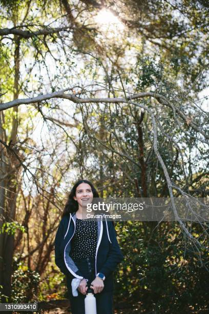 teen girl outside laughs while holding a water bottle - thousand oaks stock pictures, royalty-free photos & images