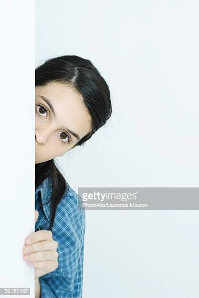 """teen girl peeking around wall, looking at camera"" - peeking stock pictures, royalty-free photos & images"