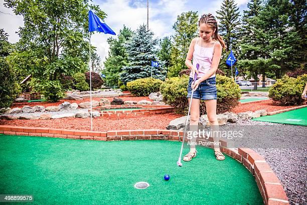 Teen girl play mini-golf