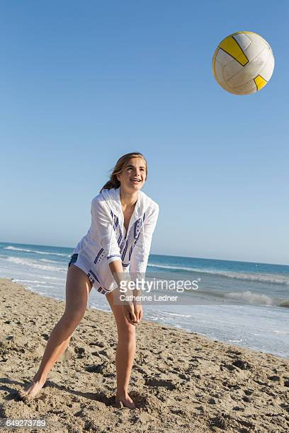 Teen girl playing beach volleyball