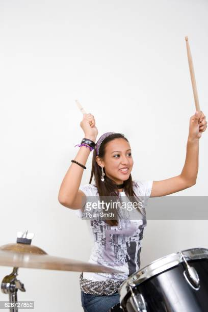 Teen girl playing drums