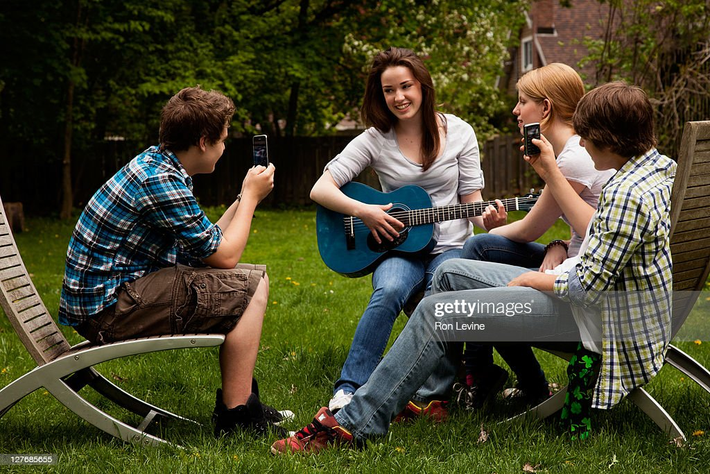 Teen girl plays guitar while friends take videos : Stock Photo