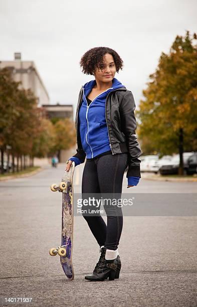 Teen girl posing with skateboard , portrait
