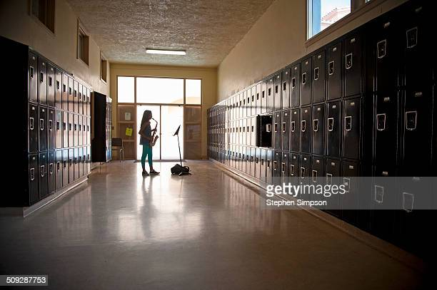 teen girl practicing saxophone in empty hallway
