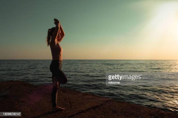 teen girl practicing yoga standing in one leg at seashore. vrikshasana pose or position of tree - yogi stock pictures, royalty-free photos & images