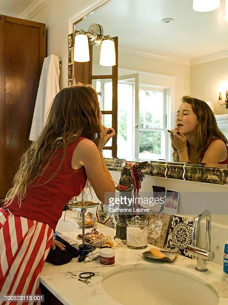 teen girl (13-15) putting on make-up in bathroom - girl in mirror stock-fotos und bilder