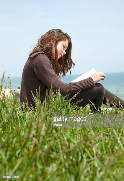 Teen girl reading by te sea