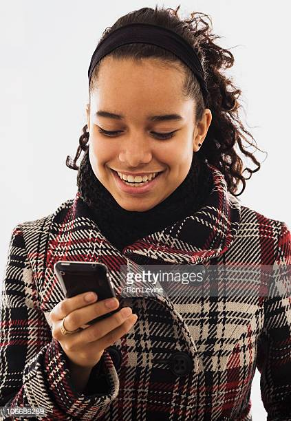 Teen girl reading text message on cellphone