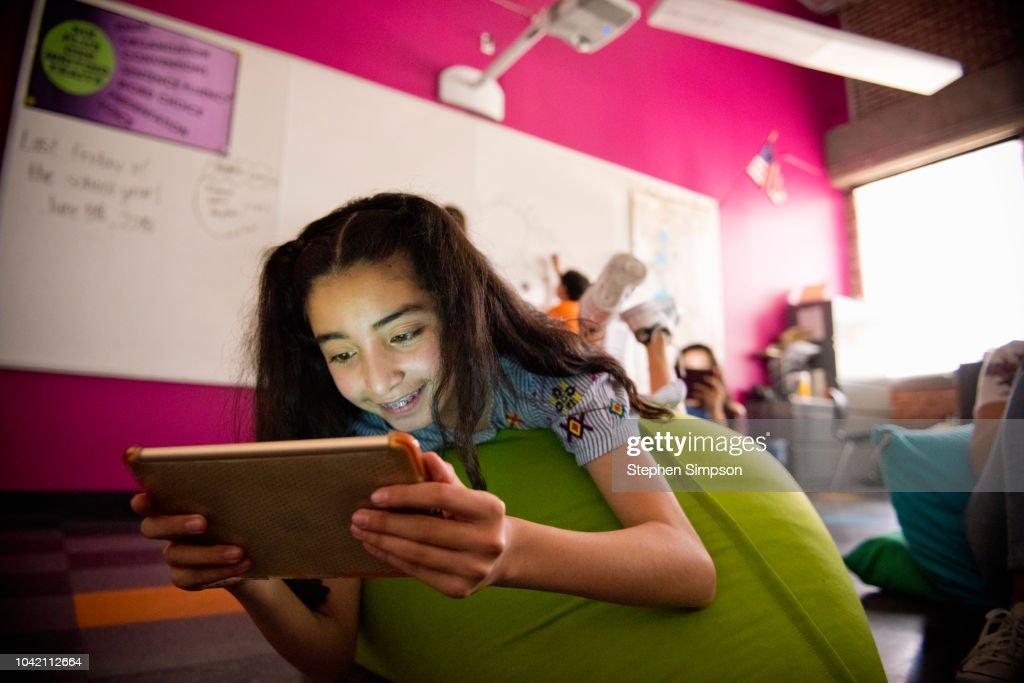 Teen girl reads tablet at modern urban charter school : ストックフォト