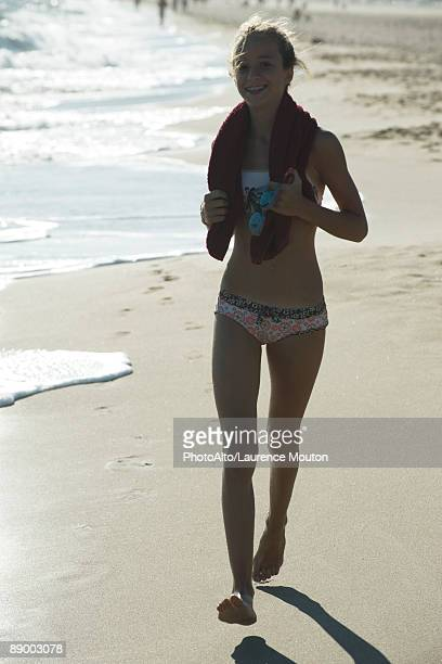 Teen girl running on beach, backlit