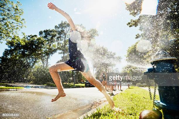 teen girl running through spray from fire hydrant on summer afternoon - fire hydrant stock pictures, royalty-free photos & images