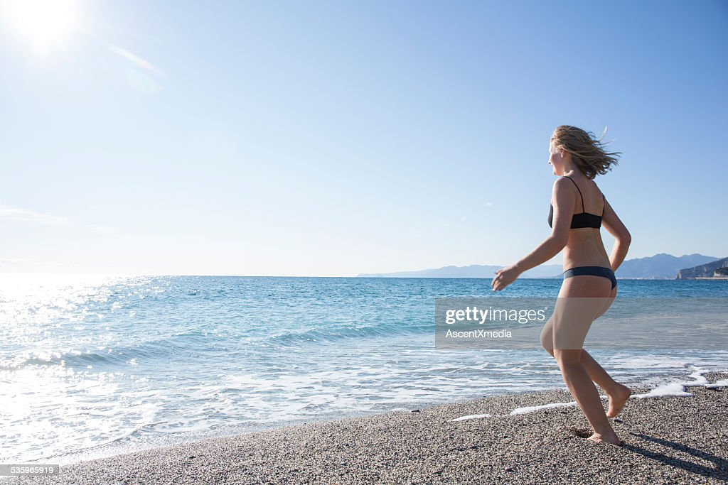 Teen girl runs across beach into waves, gentle surf : Stock Photo