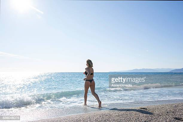 teen girl runs across beach into waves, gentle surf - thong bikini stock pictures, royalty-free photos & images