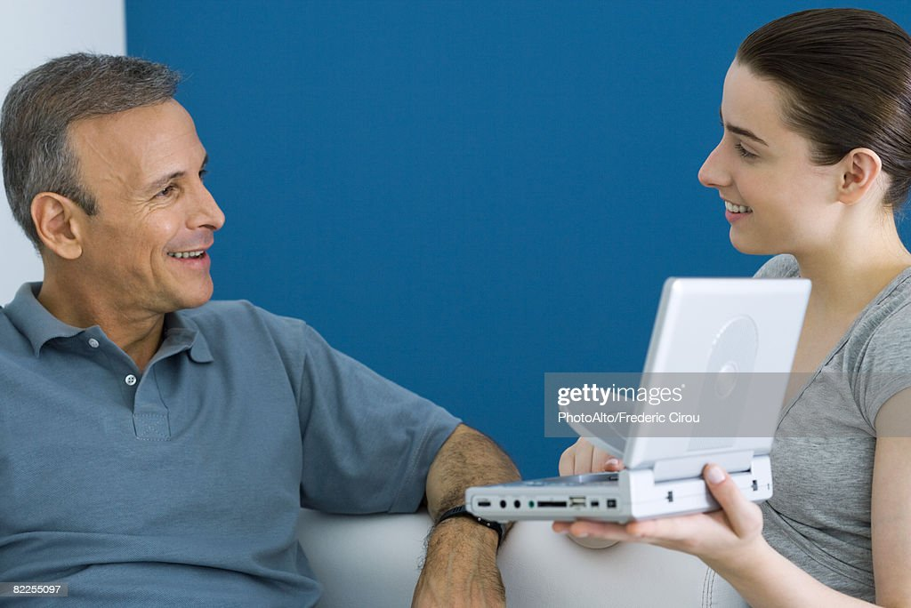 Teen girl showing her father portable DVD player, both smiling : Stock Photo