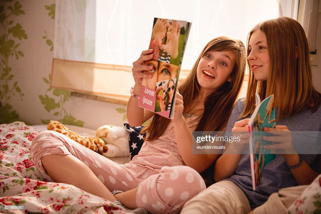 Teen girl showing her friend a new fashion magazine : Stock Photo