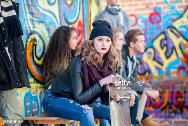 teen girl sits stoically with skateboard - clique stock photos and pictures