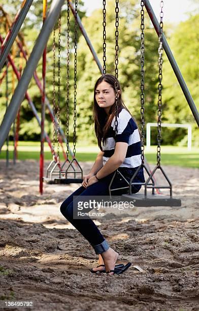 Teen girl sitting on a park swing, portrait