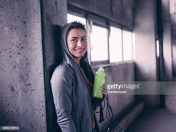 Teen girl smiling holding water bottle after a working out