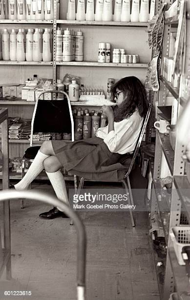 Teen girl smokes in a room with flammable cans, Juarez, Mexico, late 1980s.