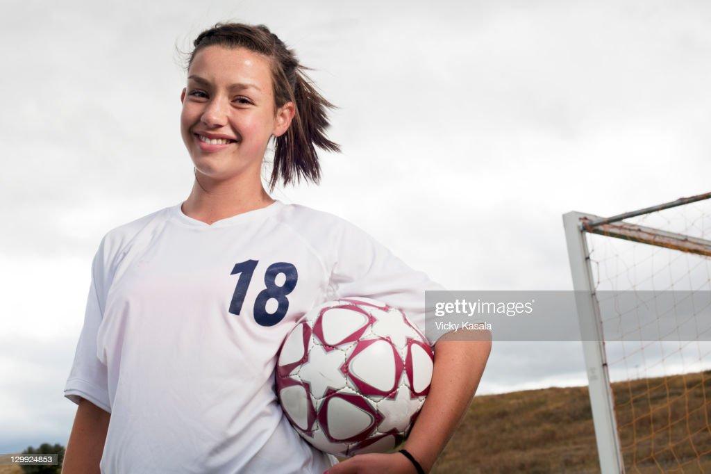 teen girl soccer player holding soccer ball : Stock Photo