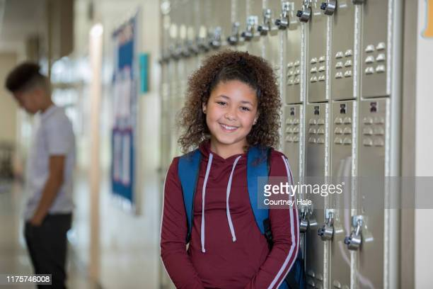 teen girl standing by lockers in corridor - charter_school stock pictures, royalty-free photos & images